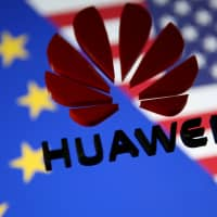 A 3D printed Huawei logo is placed on glass above displayed EU and U.S. flags in this illustration taken Jan. 29. | REUTERS