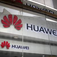 The logos of Huawei are displayed at its retail shop window reflecting the Ministry of Foreign Affairs office in Beijing in January. The head of Britain's cybersecurity agency says government oversight of Huawei has proven it can flag up security problems, suggesting he doesn't think the Chinese company needs to be banned from supplying mobile networks.   AP