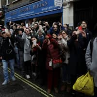 Spectators use their smartphones to record performers during the Chinese New Year parade through central London on Sunday. | REUTERS