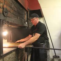 A toasty treat: Bakery owner Carl Crosby attends to pastry in the Ross Village Bakery's antique wood-fired oven in Ross, Tasmania. | KYODO