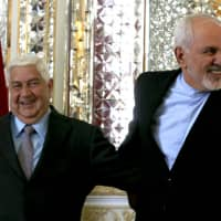Iranian Foreign Minister Mohammad Javad Zarif (right) welcomes his Syrian counterpart, Walid Muallem, in Tehran on Tuesday.   AFP-JIJI