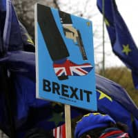 A protester holds a Brexit banner near Parliament in London on Monday. The decision by seven Labour MPs to quit on Monday could lead Labour leader Jeremy Corbyn to review his strategy on Brexit. | AP