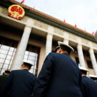 Military delegates arrive for the opening session of the National People's Congress at the Great Hall of the People in Beijing in March 2018. | REUTERS