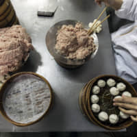 A cook places freshly-made xiaolongbao dumplings into a bamboo steamer basket in the kitchen at the Guyi Garden Restaurant in Shanghai on Jan. 27. | BLOOMBERG