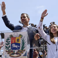 Juan Guaido, president of the National Assembly who swore himself in as the leader of Venezuela, and his wife Fabiana Rosales raise their hands during a pro-opposition protest in Caracas on Saturday.   BLOOMBERG