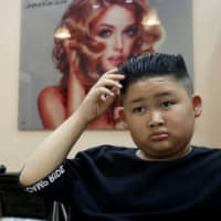 To Gia Huy, 9, examines his haircut — in the style of North Korean leader Kim Jong Un — in a salon in Hanoi on Tuesday.   REUTERS