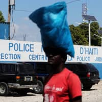 A man carries a bag in front of a main Haitian police station, where according to local media a group of foreign nationals including Americans armed with semi-automatic weapons were detained, after anti-government protests, in Port-au-Prince Monday. | REUTERS