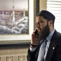 Hassan Shibly, attorney for Hoda Muthana, the Alabama woman who left home to join the Islamic State group in Syria, speaks on a phone before a news conference Wednesday in Tampa, Florida. United States Secretary of State Mike Pompeo said Muthana is not a U.S. citizen and will not be allowed to return to the United States.   AP