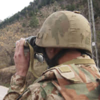A Pakistani soldier watches the movement of Indian forces on Saturday along the Line of Control from a post in Chakoti, 50 kilometers from Muzaffarabad, the capital of Pakistani Kashmir. | AP