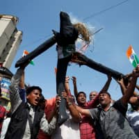 People burn an effigy depicting Pakistan as they celebrate after Indian authorities said their jets conducted airstrikes on militant camps in Pakistani territory, in Ahmedabad, India, on Tuesday. | REUTERS