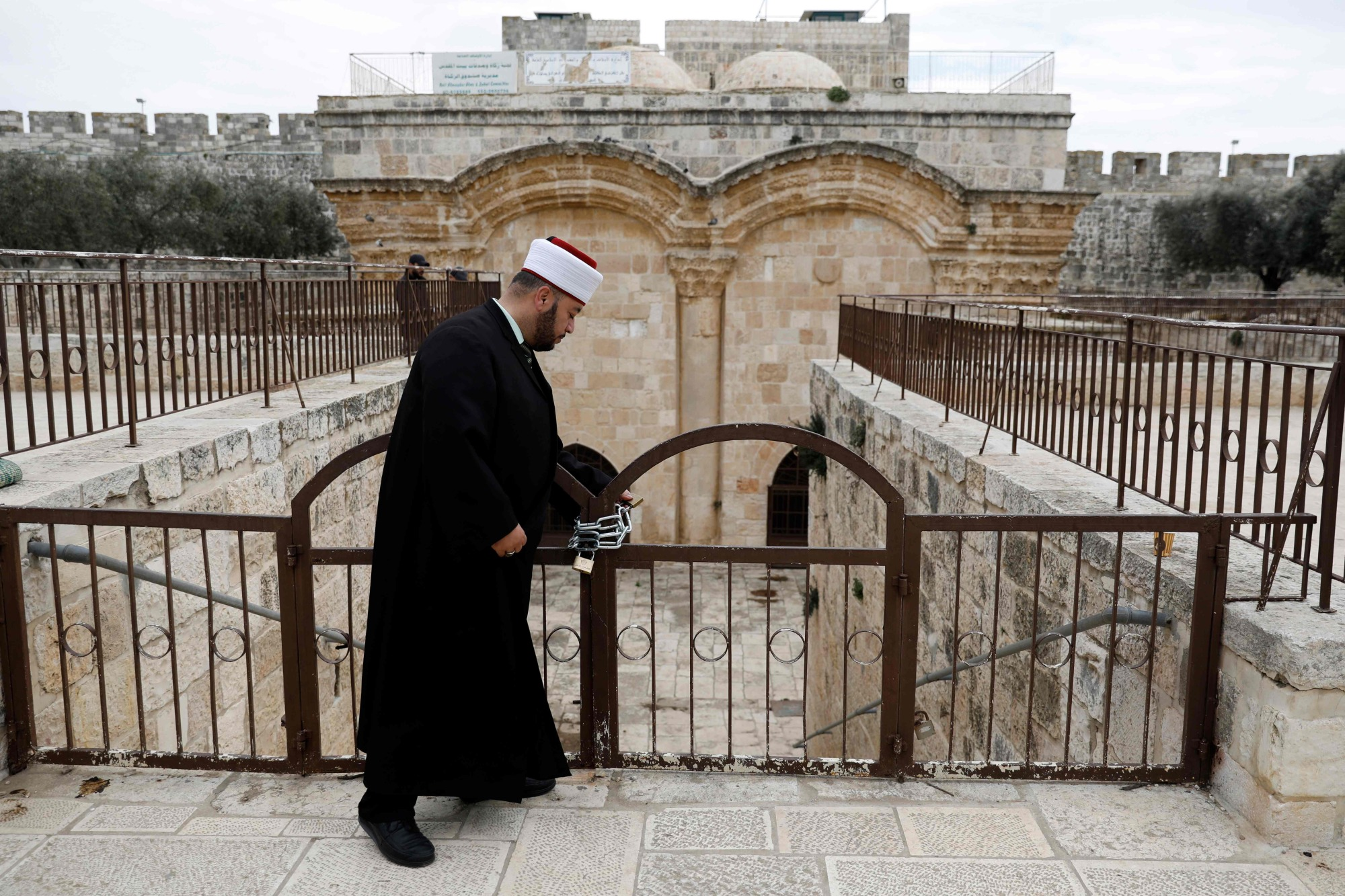 An Muslim cleric checks a gate, closed by Israeli Police, at the Al Aqsa mosque compound in Jerusalem's Old City on Feb. 18.   AFP-JIJI
