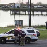 Law enforcement officers man a road block leading to a staging area during the investigation of a plane crash in Trinity Bay in Anahuac, Texas, Saturday. | BRETT COOMER / HOUSTON CHRONICLE / VIA AP
