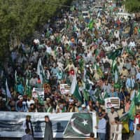 Supporters and activists of the Tehreek-e-Labbaik Pakistan party march during an anti-Indian protest in Karachi on Sunday. Indian authorities arrested dozens of Muslim leaders in raids across Kashmir and sent thousands of reinforcements to the troubled territory on Friday as Prime Minister Narendra Modi stepped up warnings to Pakistan over a suicide bomb attack. | AFP-JIJI