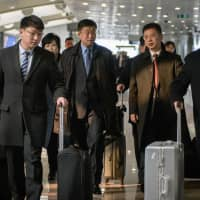 A man understood to be North Korean negotiator Kim Hyok Chol (center, blue tie) walks off an Air Koryo flight from Pyongyang, at Beijing international airport on Tuesdau. Kim Hyok Chol arrived in the Chinese capital and was expected to board a plane bound for Hanoi later in the day. | AFP-JIJI