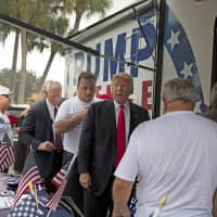 Then-Republican presidential nominee Donald Trump meets supporters organizing voter registration and support for his campaign at the Florida State Fairgrounds in Tampa in 2016. Alva Johnson (wearing Trump hat at left, a female ex-campaign staffer, is alleging in a new lawsuit filed Monday that Inside the RV, Trump kissed her without consent.   LOREN ELLIOTT / TAMPA BAY TIMES / VIA AP