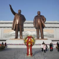 People visit the statues of former North Korean leaders Kim Il Sung (left) and Kim Jong Il on Mansu Hill to pay respects in Pyongyang on Saturday as they mark the 77th anniversary of the birth of the late Kim Jong Il. | AP