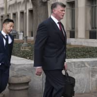 Kevin Downing (right), Paul Manafort's defense attorney, walks to the entrance of federal court on Wednesday in Washington. At left is attorney Tim Wang, another member of the defense team for Manafort. | AP