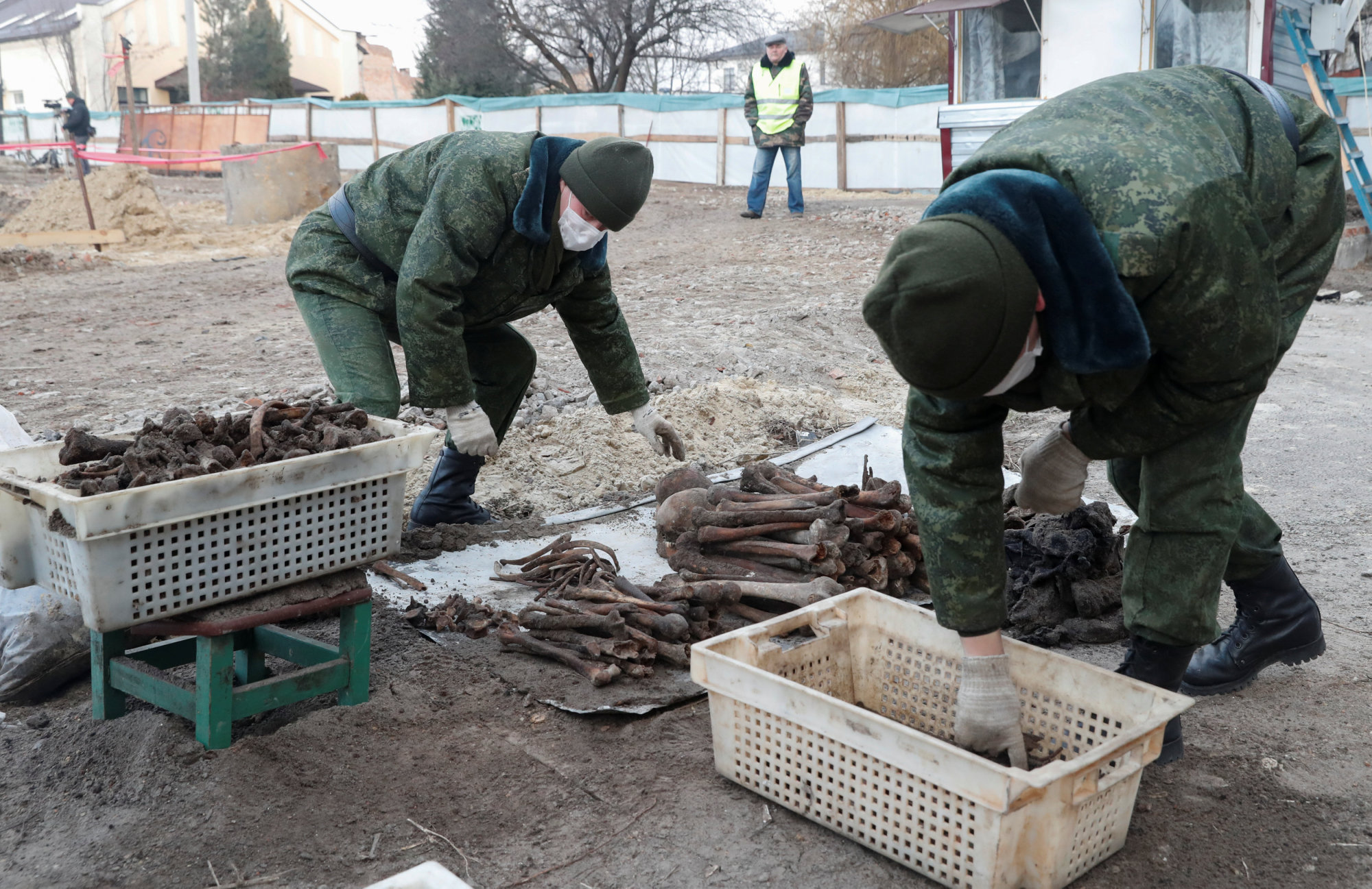 Soldiers from a special 'search battalion' of the Belarus Defense Ministry collect the remains of about 730 prisoners of a former Jewish ghetto, discovered in a mass grave at a construction site in the center of Brest, Belarus, Tuesday.   REUTERS