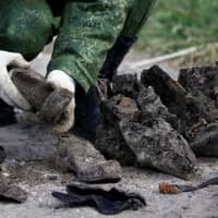 A soldier from a special 'search battalion' of the Belarus Defense Ministry takes part in the exhumation of a mass grave containing the remains of about 730 prisoners of a former Jewish ghetto, discovered at a construction site in the center of Brest, Belarus, Tuesday.   REUTERS