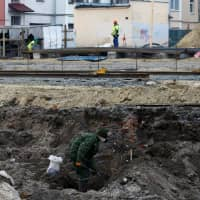 A soldier from a special 'search battalion' of the Belarus Defense Ministry takes part in the exhumation of a mass grave containing the remains of about 730 prisoners of a former Jewish ghetto, at a construction site in Brest, Belarus, Tuesday.   REUTERS