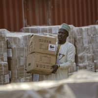 An electoral worker carries electoral materials past stacks of the papers to be used for recording results, at the offices of the Independent National Electoral Commission in Kano, northern Nigeria, Thursday.   AP