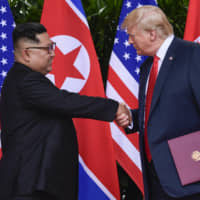 North Korea leader Kim Jong Un and U.S. President Donald Trump shake hands at the conclusion of their meetings at the Capella resort on Singapore's Sentosa Island last June.   AP