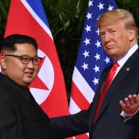 U.S. President Donald Trump meets with North Korean leader Kim Jong Un at the start of their summit at the Capella Hotel on Sentosa Island in Singapore on June 12. | AFP-JIJI