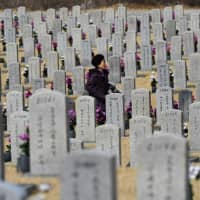 A woman walks past gravestones of South Korean soldiers killed in the 1950-53 Korean War, at the National Cemetery in Seoul on Wednesday. Hopes that U.S. President Donald Trump and North Korean leader Kim Jong Un will declare an end to the 1950-53 Korean War at the Hanoi summit have risen after South Korea suggested the two leaders could reach such an agreement. | AFP-JIJI
