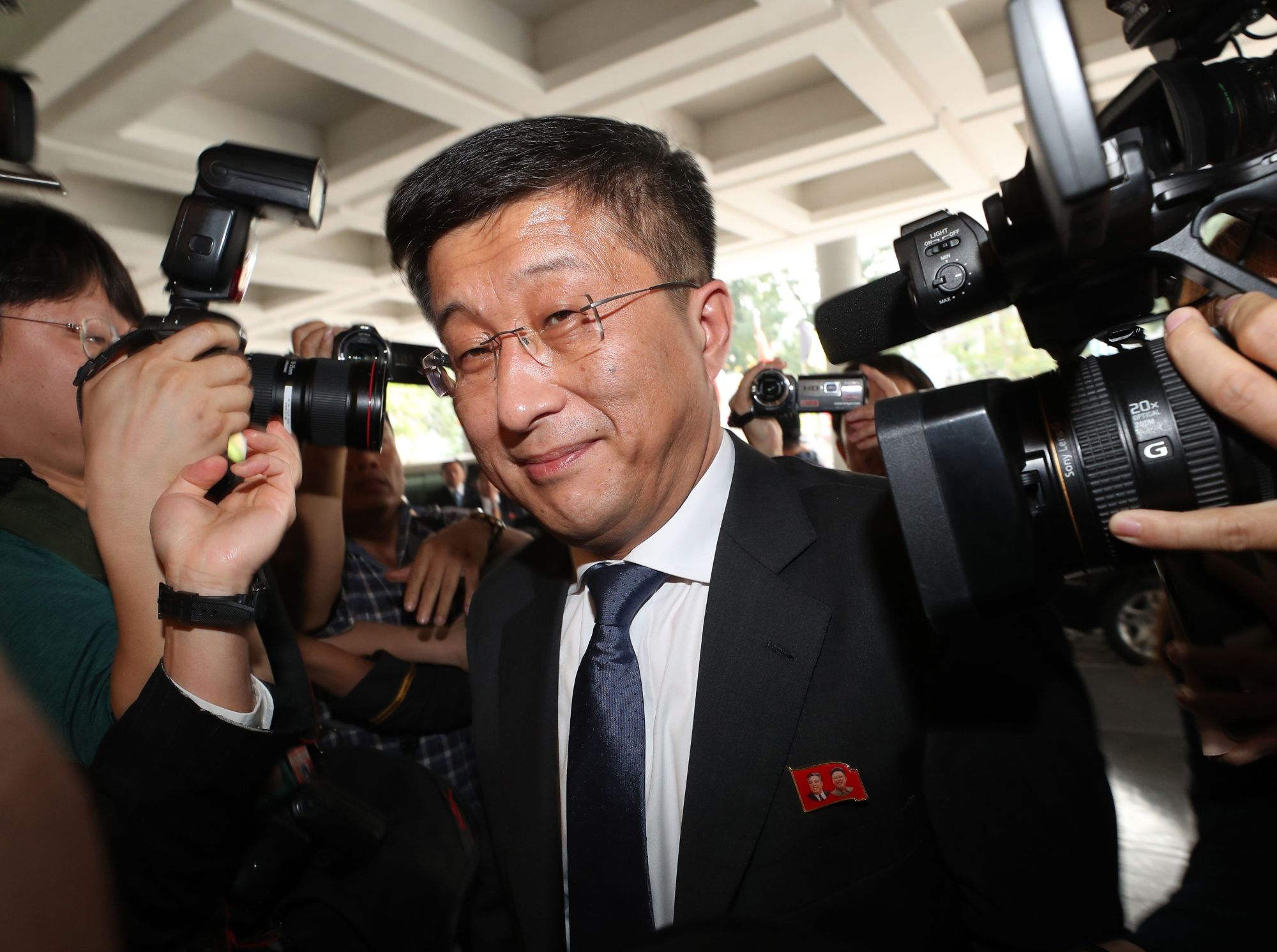 North Korea's top nuclear negotiator, Kim Hyok Chol, is surrounded by the media as he arrives for talks with U.S. counterpart Stephen Biegun in Hanoi on Thursday. | AFP-JIJI
