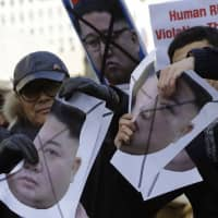 South Korean protesters and North Korean defectors tear portraits of North Korean leader Kim Jong Un during a rally near the U.S. Embassy in Seoul. The protesters were urging the United States to discuss North Korean human rights issues in the summit between U.S. President Donald Trump and Kim. | AP