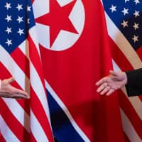 U.S. President Donald Trump shakes hands with North Korean leader Kim Jong Un at the start of their summit at a Hanoi hotel on Wednesday. | AFP-JIJI