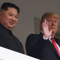 U.S. President Donald Trump waves as he and North Korean leader Kim Jong Un look out from a veranda during their historic summit at the Capella Hotel on Singapore's Sentosa Island last June. | AFP-JIJI