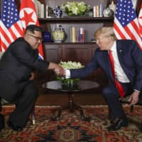 North Korea leader Kim Jong Un and U.S. President Donald Trump shake hands during their first meeting at the Capella resort on Sentosa Island in Singapore on June 12.   AP
