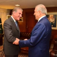 Pakistani Foreign Minister Shah Mahmood Qureshi (left) receives U.S. envoy Zalmay Khalilzad at the Foreign Ministry in Islamabad on Jan. 18. | AP
