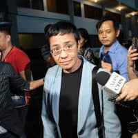 Philippine journalist Maria Ressa (center) is surrounded by the press as she is escorted by a National Bureau Investigation agent at the NBI headquarters after her arrest in Manila on Wednesday. | AFP-JIJI