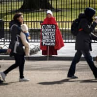 People walk past an activist dressed as a character from the TV show 'The Handmaid's Tale' during a protest over U.S. President Donald Trump's immigration policy near the White House Monday in Washington. | AFP-JIJI