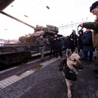 A Russian serviceman with a sniffer dog stands near a train as people attend a mobile exhibition installed on freight cars and displaying military equipment, vehicles and weapons, which, according to Russia's Defense Ministry, were captured during its Syrian campaigns, upon its arrival at a railway station in Rostov-on Don, Russia, Wednesday.   REUTERS