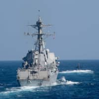 The guided-missile destroyer USS Spruance and the fast attack submarine USS Louisville sail in formation during an anti-submarine warfare exercise in the Arabian Sea on Dec. 18. | U.S. NAVY