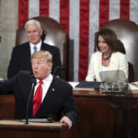 President Donald Trump acknowledges women in Congress as he delivers his State of the Union address to a joint session of Congress, as Vice President Mike Pence and Speaker of the House Nancy Pelosi watch on Tuesday.   AP