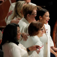 Rep. Alexandria Ocasio-Cortez (center) smiles as she joins fellow Democratic members of Congress before President Donald Trump delivers his State of the Union address to a joint session of Congress on Tuesday. | REUTERS