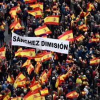 Right-wing protesters wave Spanish flags and hold a banner reading 'Sanchez, resign' during a demonstration in Madrid against Spanish Prime Minister Pedro Sanchez on Sunday. | AFP-JIJI