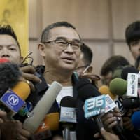 Reungkrai Leekijwatana, an official with the Thai Raksa Chart party, speaks to members of the media at the office of the Election Commission in Bangkok on Monday. | BLOOMBERG