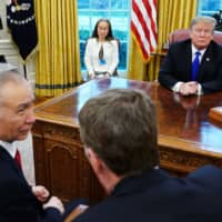 U.S. President Donald Trump listens as Chinese Vice Premier Liu He speaks with U.S. Trade Representative Robert Lighthizer in the Oval Office of the White House on Friday. | AFP-JIJI