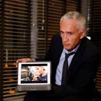 Jorge Ramos, anchor of Spanish-language U.S. television network Univision, shows a video of young Venezuelans eating from a garbage truck, while talking to the media in Caracas Monday.   REUTERS