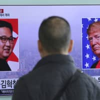 A man watches a TV screen showing images of U.S. President Donald Trump and North Korean leader Kim Jong Un during a news program at the main railway station in Seoul on Saturday. | AP