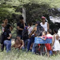 Venezuelan migrants rest under a tree near the International bridge Tienditas, on the outskirts of Cucuta, Colombia, on the border with Venezuela Tuesday. Venezuelan opposition leader Juan Guaido is moving ahead with plans to try to bring in humanitarian aid through the Colombian border city of Cucuta, where the U.S. government will transport and store food and medical supplies destined for Venezuela. | AP