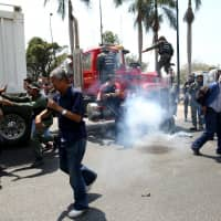 Lawmakers of the Venezuelan National Assembly and supporters of Venezuelan opposition leader Juan Guaido, who many nations have recognised as the country's rightful interim ruler, clash with security forces as they block the road on the outskirts of Mariara, Venezuela, Thursday. | REUTERS