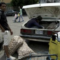A man loads his car with potatoes bought in Colombia, in San Antonio del Tachira, Venezuela, on the border with Colombia, Thursday. Opposition leaders led by self-proclaimed interim president Juan Guaido are vowing to bring in U.S. supplies of emergency food and medicine to dramatize the country's hardships under President Nicolas Maduro, who has said the country doesn't need such help. | AP