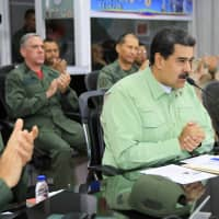 Venezuelan President Nicolas Maduro is accompanied by the military high command during a special broadcast at Tiuna Fort in Caracas Thursday. Maduro said Venezuela would shut its border with Brazil on Thursday 'until further notice' amid a tense standoff with opposition leader Juan Guaido over allowing in humanitarian aid. | VENEZUELAN PRESIDENCY / VIA AFP-JIJI