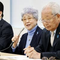 Sakie Yokota (center) speaks during a news conference in Tokyo on Sunday, along with Shigeo Iizuka (right), the head of a group of families of Japanese nationals abducted to North Korea. | KYODO